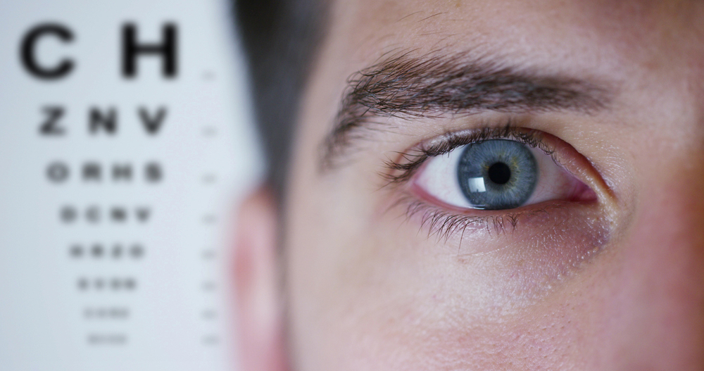 man with blue eye and eye chart
